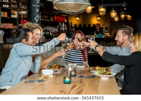 Male and female friends toasting wineglasses at restaurant table - stock photo