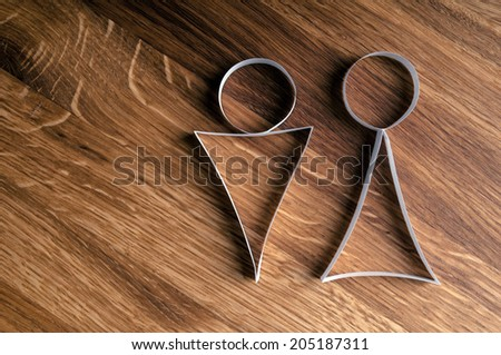Male and female gender symbols on wooden background. - stock photo