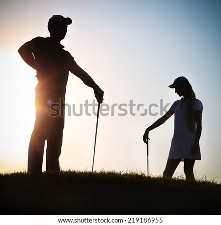 Male and female golfers playing golf at sunset - stock photo