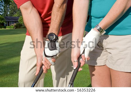 Male and female golfers practice their golf grips. Horizontally framed photo. - stock photo