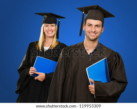 Male And Female Graduate Students Holding Book On Blue Background - stock photo
