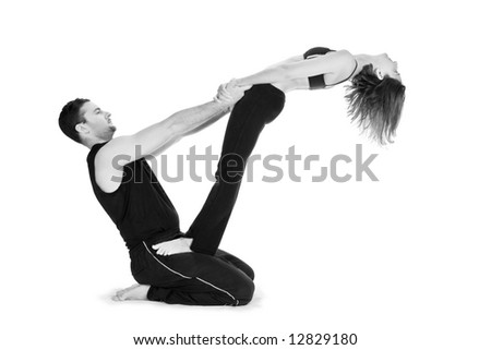 Male and female gymnasts practicing a complex double yoga pose. - stock photo