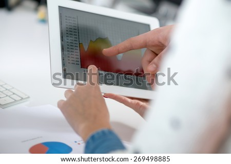 Male and female hand pointing a finger on a tablet - stock photo