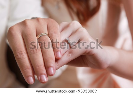 Male and female hand show golden ring with diamond in their finger.