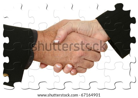 Male and female hands in suits shaking hands inside puzzle pieces. - stock photo