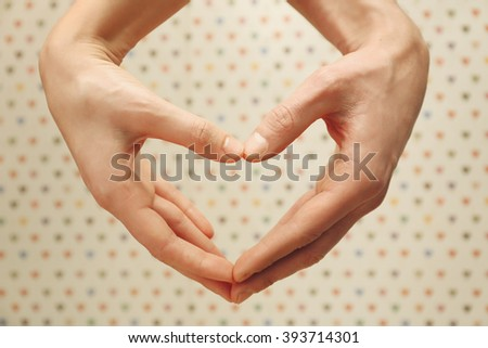 Male and female hands making heart with fingers on blurred background