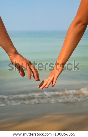 male and female hands on the beach