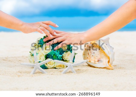 Male and female hands, two wedding rings with two starfish, wedding bouquet and a large shell on a sandy tropical beach. Blue sea in the background. Wedding and honeymoon in the tropics. - stock photo