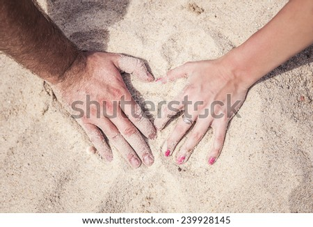 Male and female hands with rings on the sand