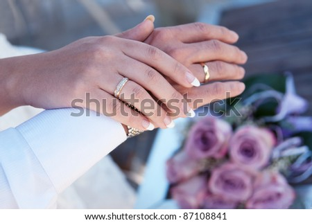 Male and female hands with wedding rings. In the background, wedding bridal bouquet.