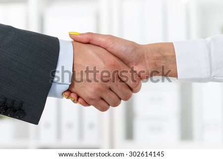 Male and female handshake in office. Businessman in suit shaking woman's hand. Serious business and partnership concept. Partners made deal, sealed with handclasp. Formal greeting gesture - stock photo