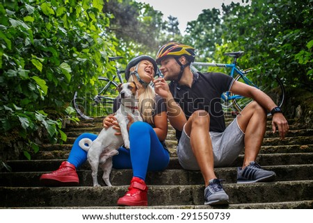 Male and female in sportswear posing on steps with their small dog. - stock photo