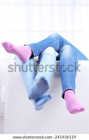 Male and female legs on sofa close-up - stock photo