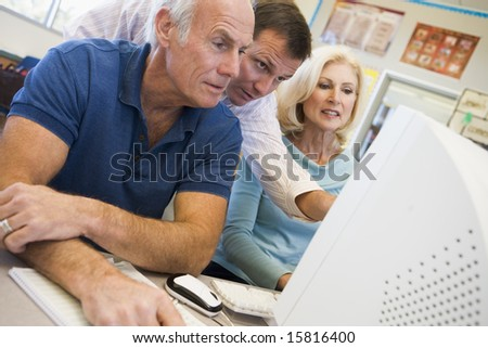 Male and female mature students working together on a computer - stock photo