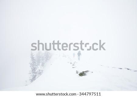 Male and female mountain climbers with huge backpacks and trekking poles having hard hiking trip during winter storm in Austrian Alps - stock photo