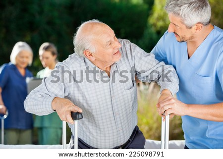 Male and female nurses helping senior people in nursing home - stock photo
