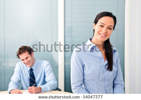 Male and female office workers, she is smiling to the camera. - stock photo