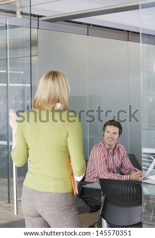 Male and female office workers talking in the office - stock photo