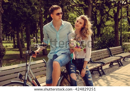 Male and female on one bicycle after dating in summer park. - stock photo