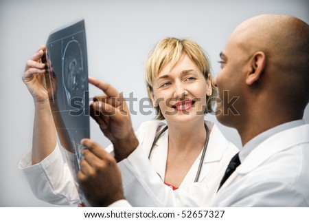 Male and female physicians holding and looking at patient xray film pointing and smiling. - stock photo