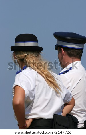 Male and female police officers standing together in summer uniform, against a blue sky. - stock photo