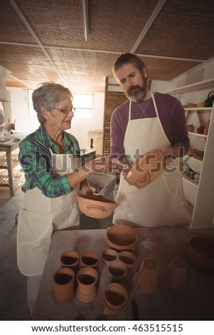 Male and female potter interacting while examining a pot in pottery workshop