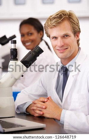 Male And Female Scientists Using Microscopes In Laboratory - stock photo