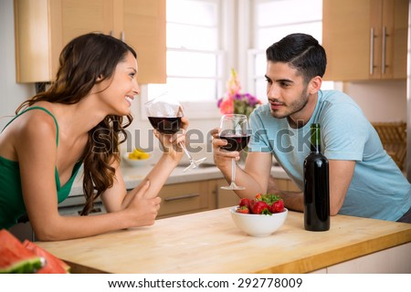 Male and female sipping red wine in the kitchen sharing a romantic gaze with chemistry - stock photo