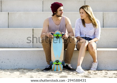 Male and female skateboarders sitting on steps at beach - stock photo