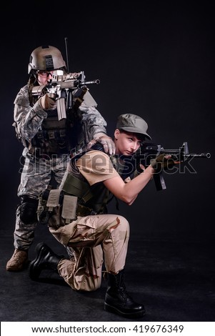 Male and female soldiers in uniform with rifles aim at target on dark background/Male and female soldier - stock photo