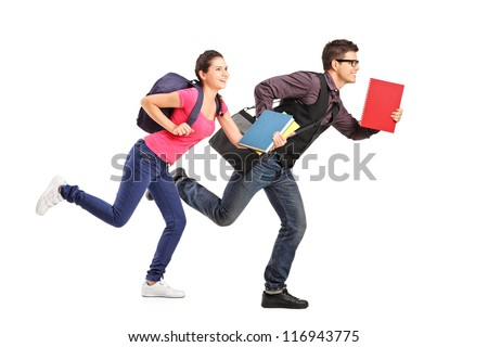 Male and female students rushing forwards with books in their hands, focus on the boy - stock photo