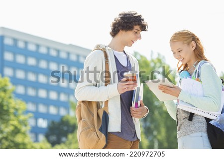 Male and female students using digital tablet at college campus - stock photo