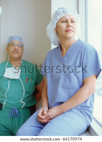 Male and female surgeons near hospital window