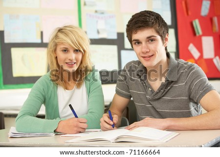 Male And Female Teenage Students Studying In Classroom - stock photo