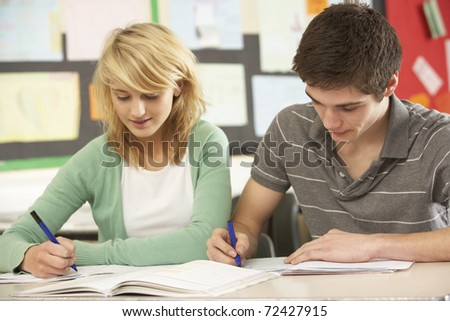 Male And Female Teenage Students Studying In Classroom