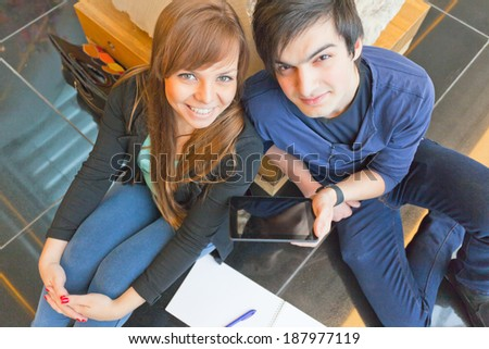 male and female university students sitting on a bench and do their homework - stock photo