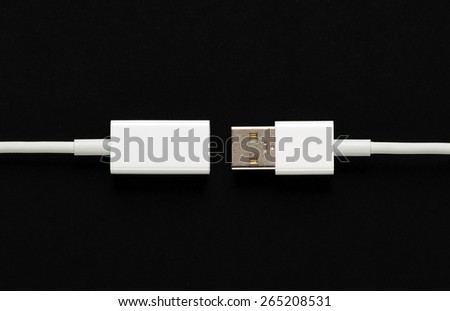 Male and female USB plugs on cables arranged facing each other over a black background in a computing and connectivity concept - stock photo