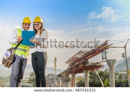 Male and female worker looking at construction plan of the bridge and discuss about it