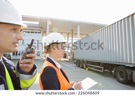 Male and female workers working in shipping yard - stock photo