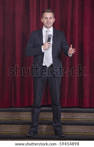 male announcer with microphone on the stage - stock photo