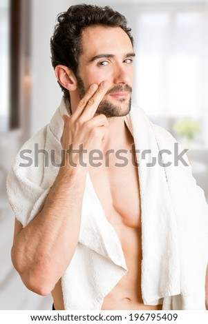 Male applying moisturizer to her face in the bathroom - stock photo