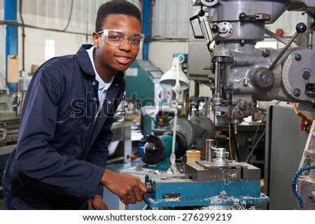 Male Apprentice Engineer Working On Drill In Factory - stock photo
