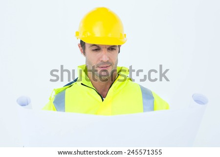 Male architect analyzing blueprint over white background - stock photo
