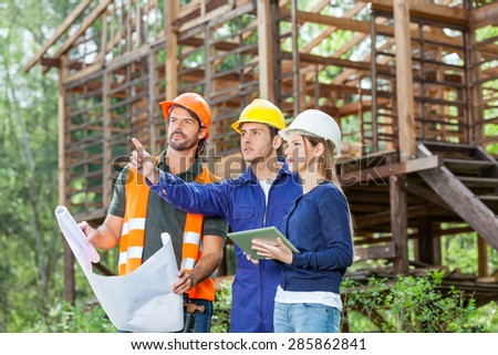 Male architect explaining something to colleague while analyzing blueprint at construction site - stock photo