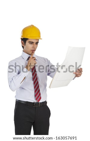 Male architect holding a blueprint and thinking - stock photo