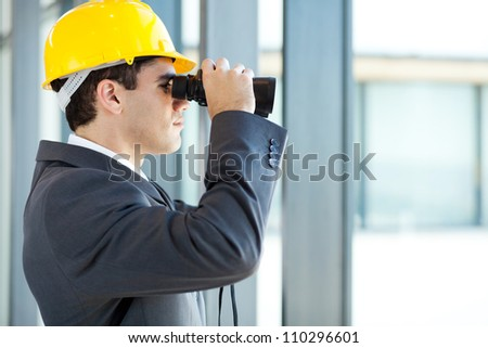 male architect looking at construction site with binoculars - stock photo