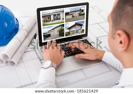 Male architect looking at designs of house on laptop at office - stock photo