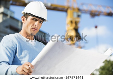 Male architect reviewing blueprint at construction site - stock photo