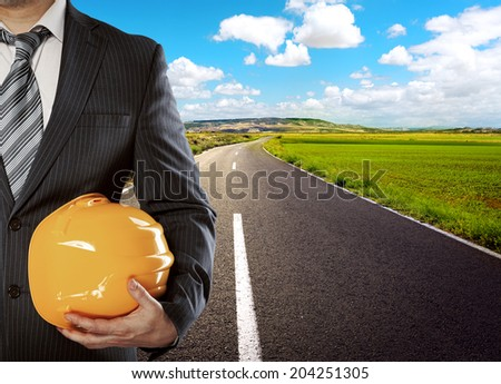 Male architect standing on asphalt road with helmet. Concept of start of new industrial deal.  - stock photo