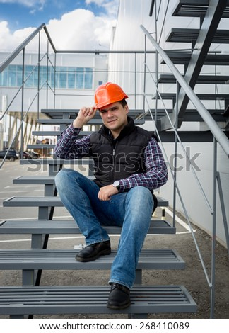 Male architect wearing red hard hat sitting on metal staircase at factory - stock photo